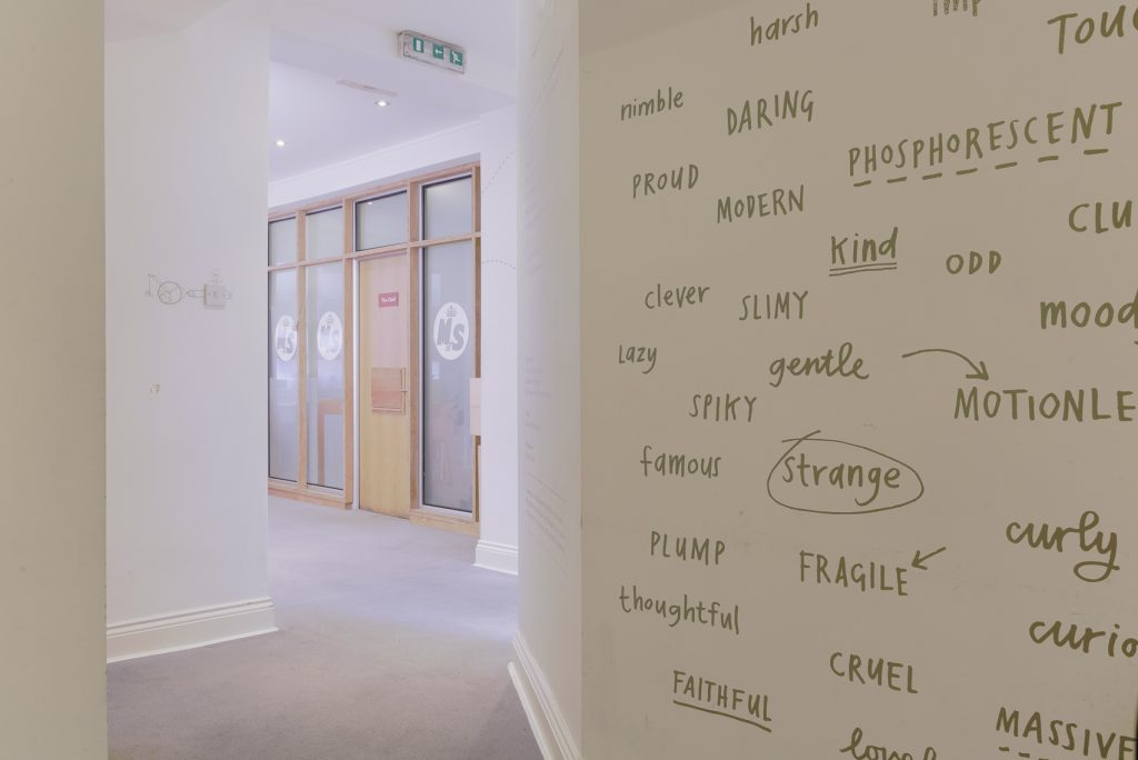 A wall decorated with words in the workshop space