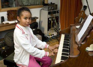 Girl at piano in recording studio - Communion Records (photo: Miriam Douglas)