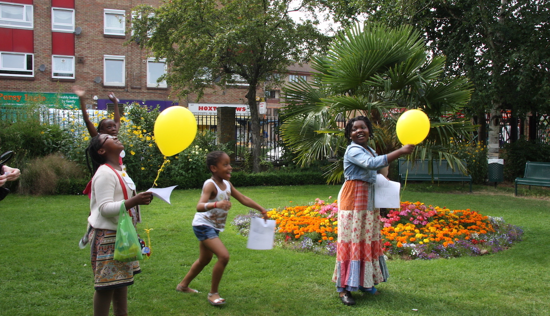 Children release balloons with letters attached
