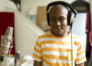Boy wearing earphones in recording studio (photo: Miriam Douglas) - Share More Air
