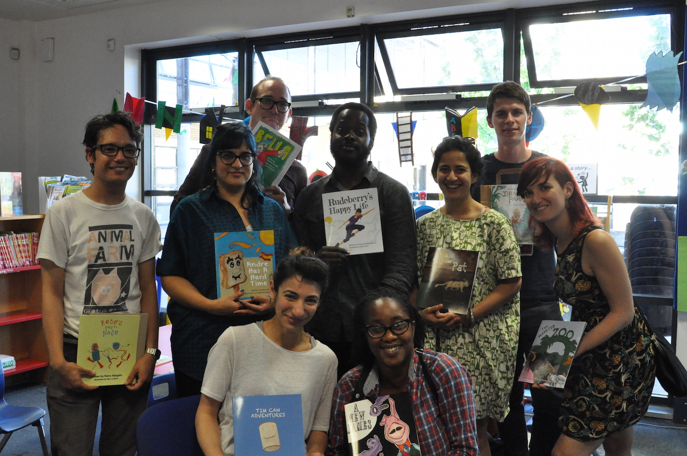 Volunteer illustrators posing with their books