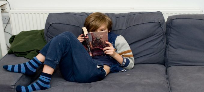A young person from the Ministry of Stories enjoys reading a book curled up on the sofa