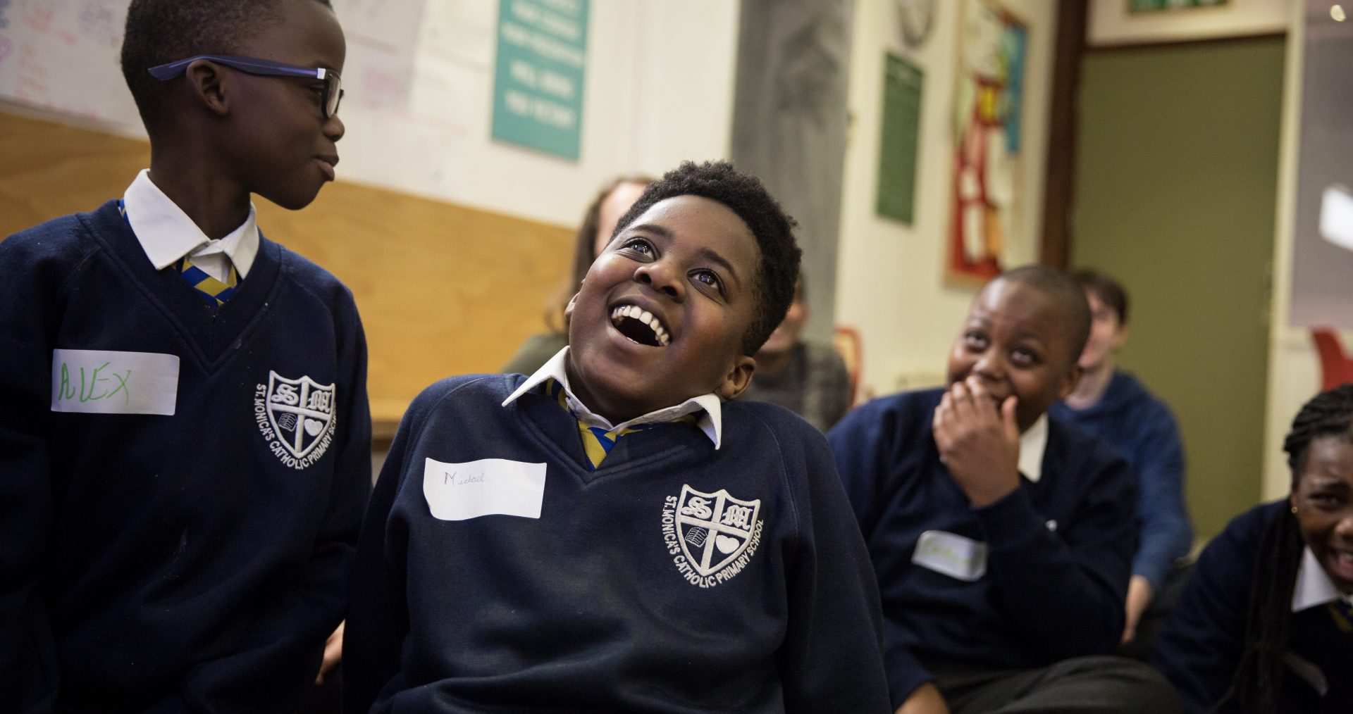 Three young boys laugh while sitting in the ministry of Stories