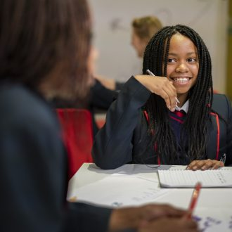 Young writer sitting behind a desk smiling at a volunteer mentor.
