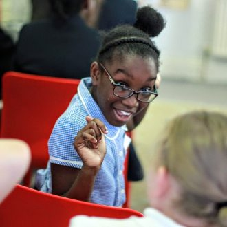 Young girl turning in chair to talk