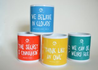 "Four mugs in bright colours, featuring the four quotes ""we can be weird here"", ""we believe in clouds"", ""the secret is cinnamon"" and ""think like an owl"""