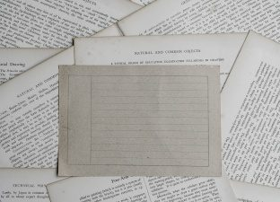 A blank writing sheet sits on tops of lots of written letters