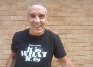 Joe smiles at the camera standing in front of a brick wall, wearing a Parkinson's Disease fundraising t-shirt