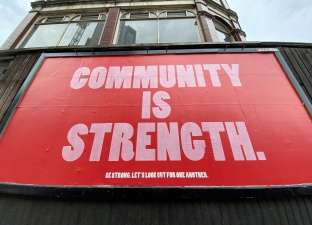 A large billboard with red and pink text proclaims 'community is strength' on Seven Sisters Road, London, UK